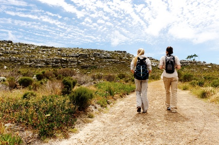 adventure holiday: two girls walking outdoors and having fun exploring the wilderness