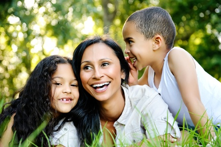 hispanic people: happy family outdoors on the grass in a park. mom and two children smiling