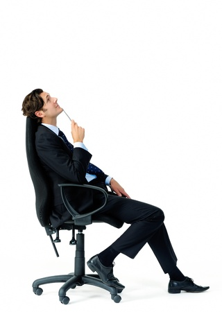 Suit wearing businessman ponders and looks overhead while holding a pen 免版税图像