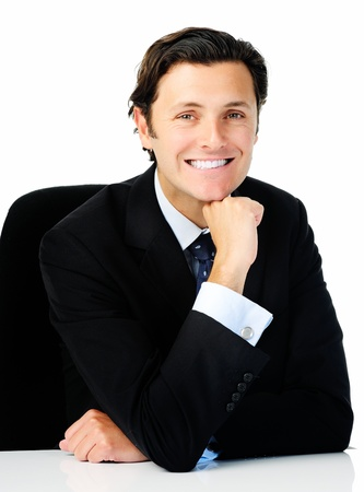 honest: Smart looking businessman leans forward on the desk and rests his chin on his hand while he poses for a portrait