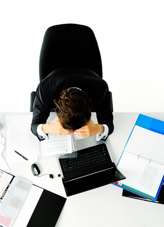 Businessman in suit puts his face in his hands when he is overwhelmed with too much work Stock Photo - 11900435
