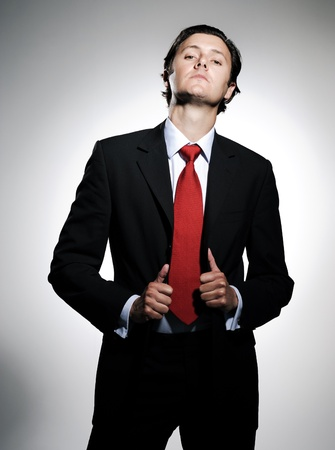 lapels: Highly successful business man in suit poses pulling his suit lapels with an arrogant tilt to the chin Stock Photo