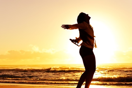 vitality: carefree woman dancing in the sunset on the beach. vacation vitality healthy living concept
