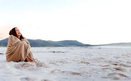 cold woman wraps blanket over hersolf while sitting on the beach after sunset. copyspace provided by panoramic image Stock Photo - 11900124