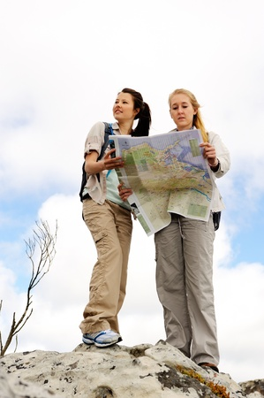 portrait orientation: two cheerful women hiking outdoors and consulting their map for the direction in which to travel Stock Photo