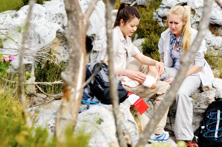 A woman has sprained her ankle while hiking, her friend uses the first aid kit to tend to the injury photo