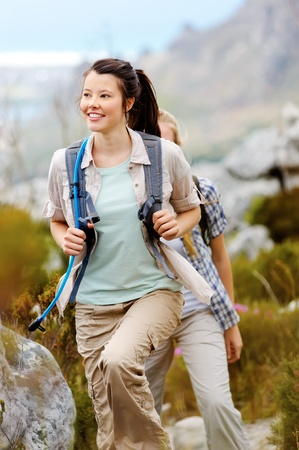 Carefree brunette girl walks outdoors hiking and exploring. she is cheerful and happy photo