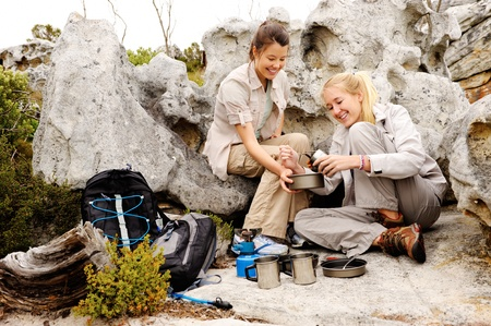 two girls open a can of baked beans while they are camping and hiking in the wilderness photo
