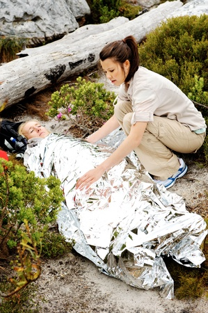 blankets: A woman is injured while hiking outdoors. her friend has covered her with and emergency blanket and checks on her using a first aid kit
