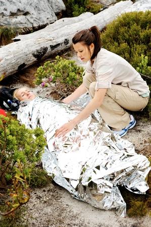 Una mujer se lesiona mientras está al aire libre, senderismo. su amiga la ha cubierto con una manta y de emergencia y los controles sobre su uso de un botiquín de primeros auxilios