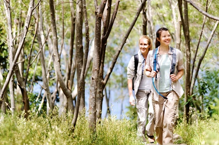 Women walking outdoor in the woods, happy exploring and adventure lies ahead for these wilderness trekking friends Stock Photo - 11900355