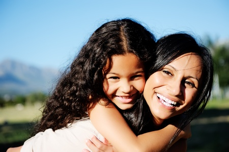 two generation family: mom and daughter have fun outdoors, smiling and piggyback in the sunshine Stock Photo