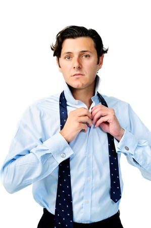 formal dressing: Handsome caucasian man buttons his top button before tying his necktie