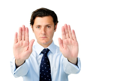 resist: Displeased businessman holds both hands up to show a stop signal