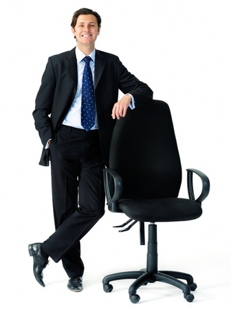 chances: Smart looking businessman leans on an empty office chair to indicate an open position, suitable for recruitment campaigns