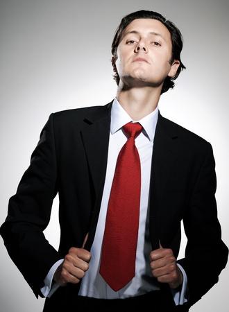 Hombre de negocios de gran éxito en el juego plantea tirar las solapas traje con una inclinación arrogante de la barbilla Foto de archivo