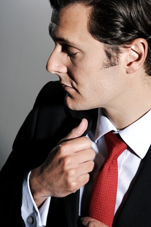 man looking down: Close up portrait of a businessman with a red tie, holding on to his lapels Stock Photo