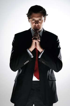 Thinking caucasian man in a business suit in dramatic lighting to convey the sinister side of enterprise Stock Photo - 11900390