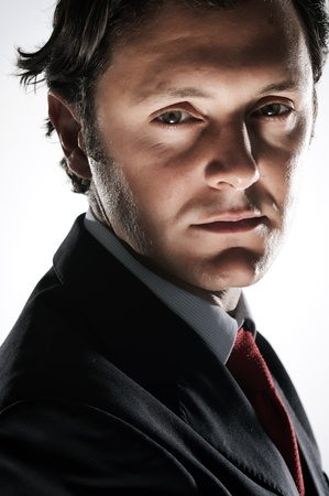sinister: Serious, devious looking businessman in studio