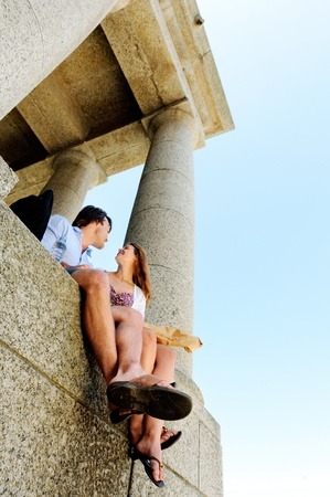 worl: a tourist couple relaxes with some bread as they take in the sights of an old monument while they travel the worl