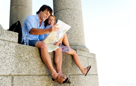 getaways: Pretty woman leans on her husband as he consults a map while on holiday