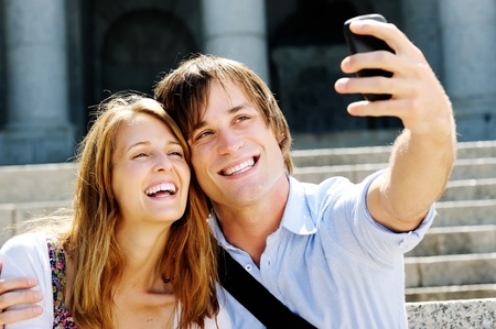 couple take a picture together while visiting a tourist attraction, smiling and having fun photo