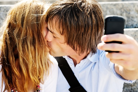 Man uses his mobile phone to snap a picture of him and his girlfriend kising photo