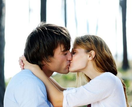 young couple kiss: joven y bella al aire libre par de besos en el bosque, el verdadero amor y pasi�n Foto de archivo