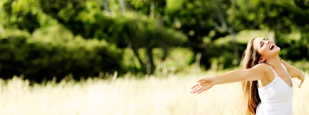 young girl dances in a field in summertime having fun