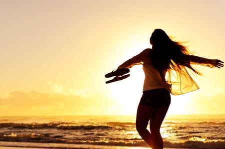 zorgeloze vrouw dansen in de zonsondergang op het strand. vakantie vitaliteit gezond leven concept van