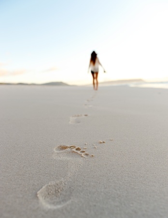 footprints in the sand: woman walks alone on a deserted beach, solitude, serene, lonely concept. carefree vacation in nature