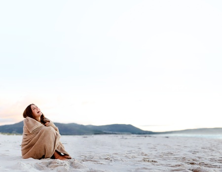 cold woman wraps blanket over hersolf while sitting on the beach after sunset. copyspace provided by panoramic image Stock Photo - 11900015