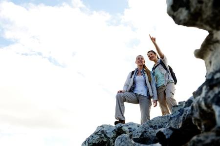 bewonderen: Gelukkige vrouwen wandelaars staan op de top van een rots en genieten van het uitzicht