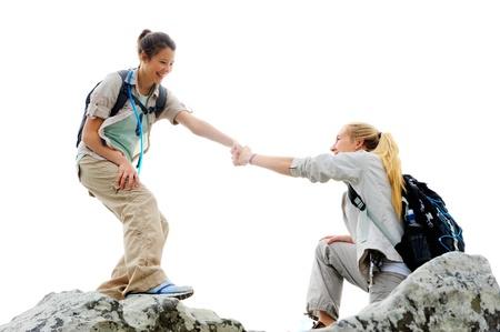 climber: Wandelen vrouw helpt haar vriend klim op de rots, outdoor lifestyle concept