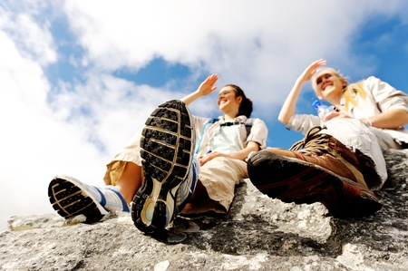 trekking: two women take a break from trekking and rest on a rock outdoors