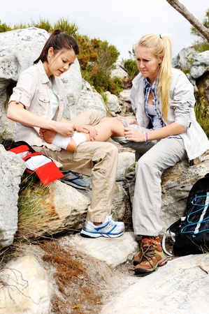 beautiful ankles: A woman has sprained her ankle while hiking, her friend uses the first aid kit to tend to the injury Stock Photo