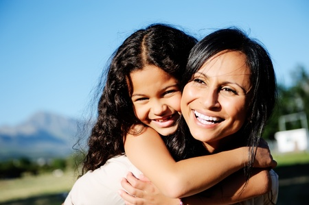mom and daughter have fun outdoors, smiling and piggyback in the sunshine Stock Photo - 11900197