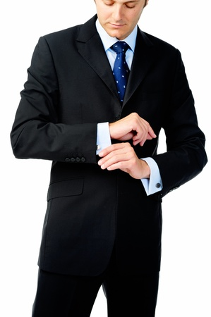 adjust: Businessman looks down to adjust his cufflinks in studio, isolated on white Stock Photo