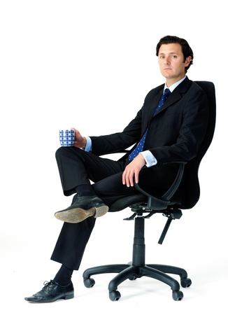 Male office worker seats in his chair, holding a mug of coffee photo