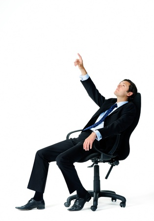 leans: Businessman leans back on his office chair and points up into the air, trying to visualise something