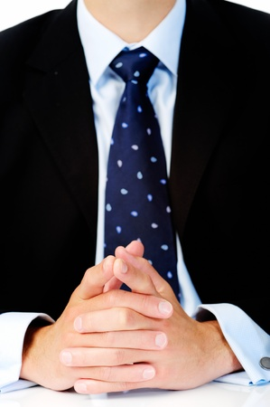 body language: Close up of a man in a suit with his hands clasped in front of him