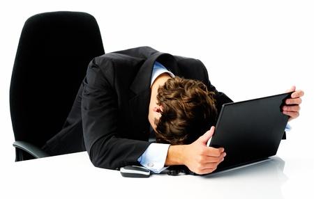 Zakenman in pak legt zijn hoofd op zijn laptop, toen hij niet aan zijn doel