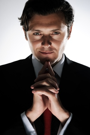 deceit: Evil looking businessman clasps his hands under his chin, in dramatic lighting Stock Photo