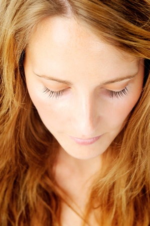 Close up portrait of a redhead caucasian woman looking down, with barely any make up - a top down perspective photo