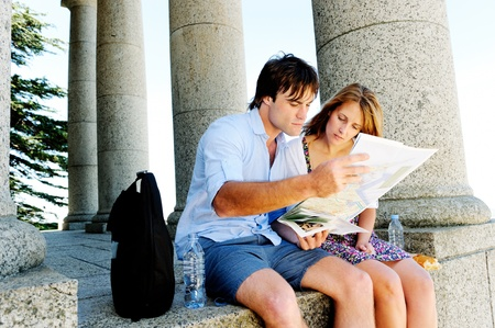 find out: couple use a map to find out where they are. young couple traveling and exploring old ruins, temples and monuments