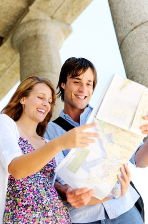 traveller: excited young couple traveling, they look at a map while visiting an old tourist attraction monument