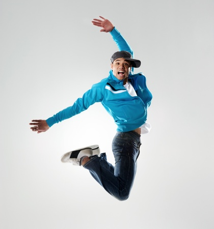 hip hop dance: dancer jumps into the air and holds a pose, motion, movement and emotion all captured in this image