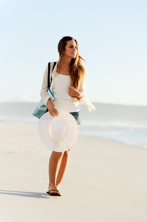 woman walking: girl walking along the shoreline with beach hat and bag