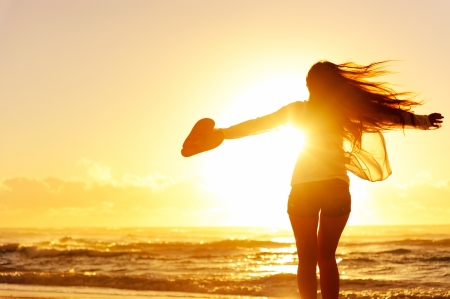 freedom girl: carefree woman dancing in the sunset on the beach. vacation vitality healthy living concept