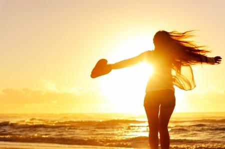 unbeschwerte Frau tanzen in den Sonnenuntergang am Strand. Urlaub Vitalität gesund leben-Konzept Standard-Bild